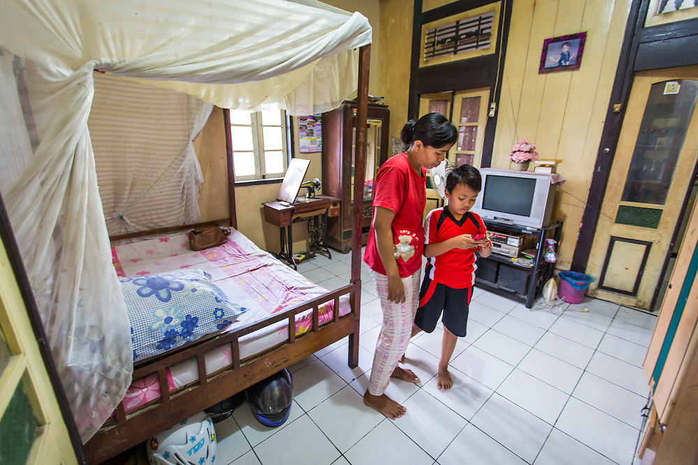 CAPTION: Mukahaynah in her family home with her youngest son, Sahrul. LOCATION: Tapak, Semarang, Indonesia. INDIVIDUAL(S) PHOTOGRAPHED: Mukhayanah Siyam (left) and Sahrul Siyam (right).