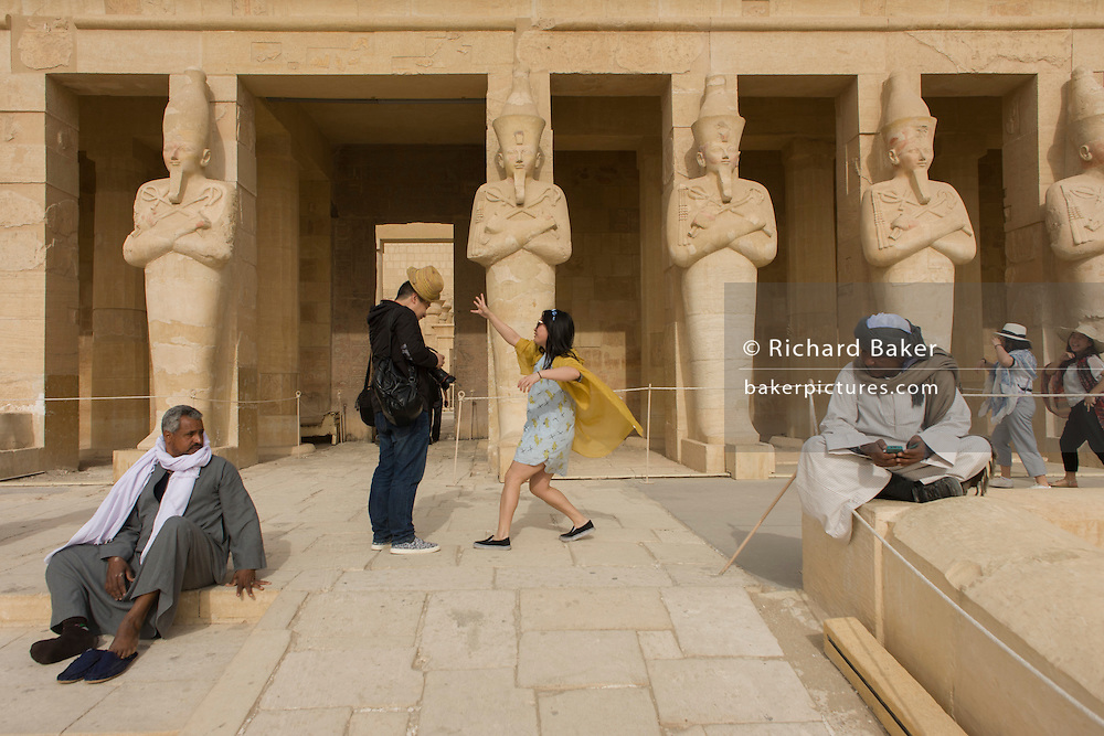 """A Chinese-speaking tourist group enjoy the experience of visiting the ancient Egyptian Temple of Hatshepsut near the Valley of the Kings, Luxor, Nile Valley, Egypt. The Mortuary Temple of Queen Hatshepsut, the Djeser-Djeseru, is located beneath cliffs at Deir el Bahari (""""the Northern Monastery""""). The mortuary temple is dedicated to the sun god Amon-Ra and is considered one of the """"incomparable monuments of ancient Egypt."""" The temple was the site of the massacre of 62 people, mostly tourists, by Islamists on 17 November 1997."""