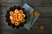 Apricot halves with sugar syrup in black bowl, above view.