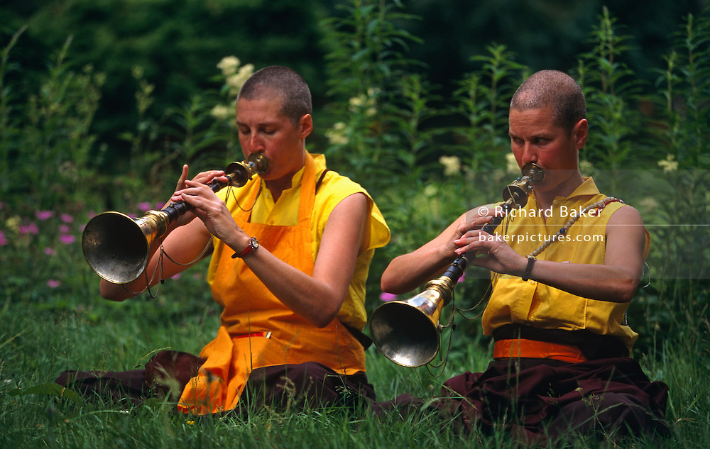 Usually played in pairs for morning and evenings calls to prayer, preludes, and processions, two western nuns following Tibetan-Buddhism play their Rag-Dung (brass trumpets) in a garden at the Kagyu Samye Ling Monastery and Tibetan Centre in Eskdalemuir, Scotland. One nun looks across to check finger positions of her fellow-player and they are sat cross-legged on the lush grass surrounded with flowers and tall plants. The Rag-Dung is the most spectacular of Tibetan ritual copper horns and some are up to twenty feet long. With a deeply resonant sound it is relatively easy to play. Those following this branch of Buddhism arrive in the Scottish wilderness for isolated Retreat periods, for short-term spiritual relaxation or to follow Tibetan teaching methods for discovering inner-peace, through prayer and meditation.