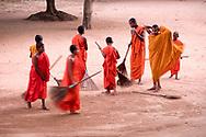 Kandy, Sri Lanka. Novice Buddhist monks sweep the monastery courtyard