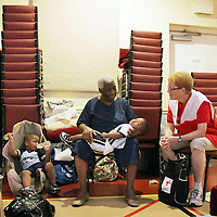 Florence Topping, center, talks with Red Cross Volunteer Eilene Guy, right, about her evacuation in preparation for Hurricane Irene, with her great grandchildren, My'Mir Morris, 2, left, Tyler Morris, 2, sleeping, and Miricha Morris, 3, not pictured.