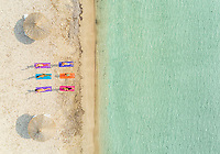 Aerial view of group of people doing yoga on colourful mats on the beach.
