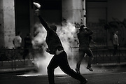"""Athens, Greece - A demonstrator throwing a stone surrounded by tear gas. Greek economical crisis started in 2008. The so-called Austerity measures imposed to the country by the """"Troika"""" (European Union, European Central Bank, and International Monetary Fund) to reduce its debt, were followed by a deep recession and the worsening of life conditions for millions of people. Unemployment rate grew from 8.5% in 2008 to 25% in 2012 (source: Hellenic Statistical Authority). <br /> Bruno Simões Castanheira"""