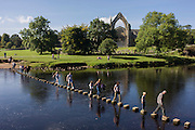 Families risk falling in the River Wharfedale while walking over the stepping stones at Augustinian Bolton Priory, North Yorkshire.