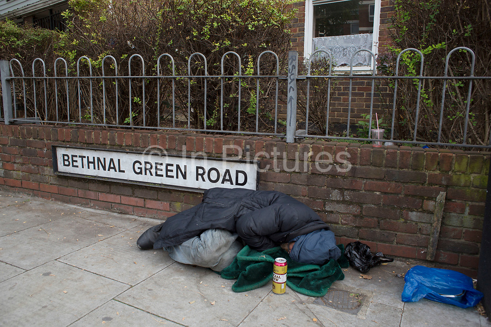 Homeless man and street drinker sleeping beside the street sign for Bethnal Green Road in East London, UK. This area is know for it's mix of creative and artistic people as well as acute poverty.