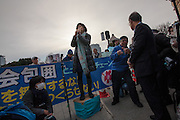 A woman makes a speech at a rally to protest the construction of a new US military base at Henoko in Okinawa outside the Japanese National Diet building, Nagatacho, Tokyo, Japan Sunday January 25th 2015. Organisers say 7,000 people joined the protest forming a human chain around the Assembly Building.