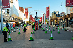 © Licensed to London News Pictures. 18/04/2021. LONDON, UK.  Security staff lay out cones to create walking lanes on Wembley Way as part of new Covid-safe crowd control procedures to manage spectators exiting Wembley Stadium for the FA Cup semi-final match between Leicester City and Southampton.   4,000 local residents have been invited to attend the match, the largest number of spectators attending a match in a UK stadium for over a year.  Covid-19 testing will take before and after the match and data gathered will be used to plan how all sports tournaments can escape lockdown.  Photo credit: Stephen Chung/LNP