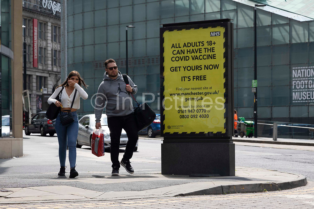A man and a woman carrying luggage and shopping bags pass by a public health notice advising people over the age of 18 that theyre eligible for a free Covid-19 vaccination on 25th July, 2021 in Manchester, United Kingdom. In the face of rising infection rates in young people, Public Health England data shows that Coronavirus vaccine uptake in that demographic has levelled off, with less than 60% of those aged 18 to 25 having received their first jab.