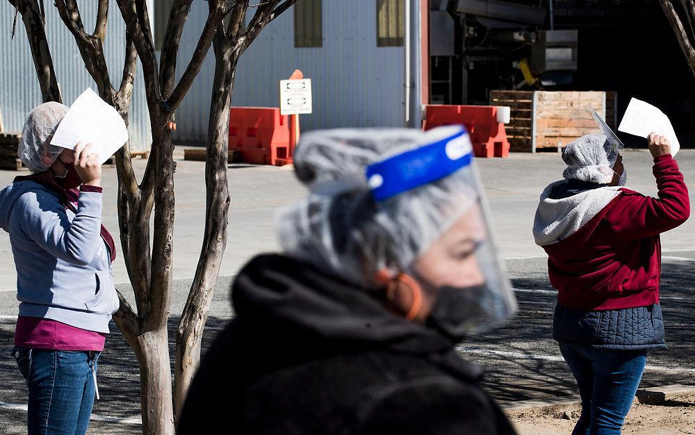 Farmworkers wait in line at a vaccination clinic organized by the Santa Clara County Public Health Department at Christopher Ranch in Gilroy, Calif. U.S., on March 4, 2021.