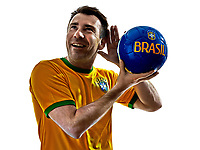 one man with Brazilian jersey listening to soccer ball isolated in white background