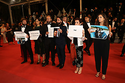 Colombian director Franco Lolli (3-R) holds up a sign to protest against the assassination of Colombian documentary filmmaker Mauricio Lezama as guests attend the screening of Sorry We Missed You during the 72nd annual Cannes Film Festival on May 16, 2019 in Cannes, France. Photo by Shootpix/ABACAPRESS.COM