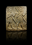 Photo of Hittite monumental relief sculpted orthostat stone panel from the Herald's Wall. Basalt, Karkamıs, (Kargamıs), Carchemish (Karkemish), 900-700 B.C. Military parade with soldiers. Anatolian Civilisations Museum, Ankara, Turkey<br /> <br /> Two helmeted soldiers marching soldiers in short skirts carry the shield on their backs and the spears in their hands.  <br /> <br /> Against a black background. .<br />  <br /> If you prefer to buy from our ALAMY STOCK LIBRARY page at https://www.alamy.com/portfolio/paul-williams-funkystock/hittite-art-antiquities.html  - Type  Karkamıs in LOWER SEARCH WITHIN GALLERY box. Refine search by adding background colour, place, museum etc.<br /> <br /> Visit our HITTITE PHOTO COLLECTIONS for more photos to download or buy as wall art prints https://funkystock.photoshelter.com/gallery-collection/The-Hittites-Art-Artefacts-Antiquities-Historic-Sites-Pictures-Images-of/C0000NUBSMhSc3Oo