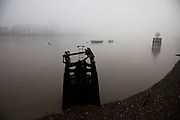Thick fog over London making a peaceful yet eerie landscape atmosphere as structures appear and disappear over the River Thames. This modern art sculptute lends an extra oddness. Modern and old industrial and commercial architecture is releaved through a mist which lasted tthrough the entire day.
