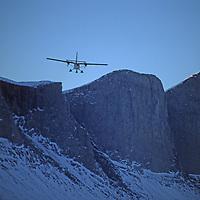 BAFFIN ISLAND, NUNAVUT, CANADA. Ski equipped Twin Otter bush plane flies over unnamed granite crags above Stewart Valley.