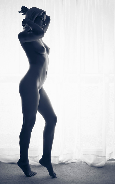 Full length of nude woman standing at drapes in front of window