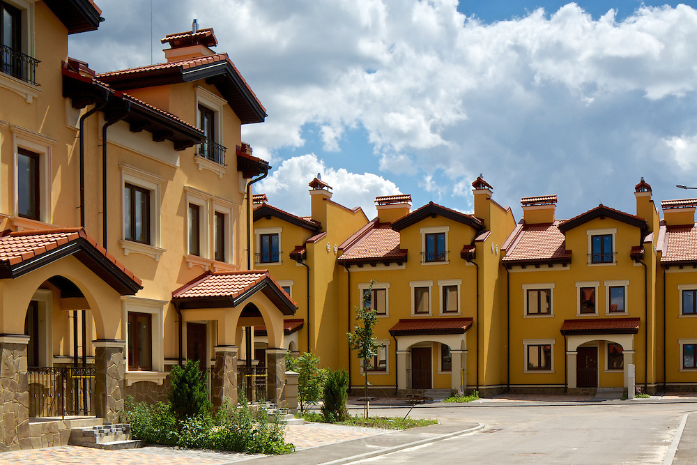 """Townhouses real estate in """"Italian Village"""" residential development project in Kyiv, Ukraine. Exterior view with the daylight and cloudy sky."""