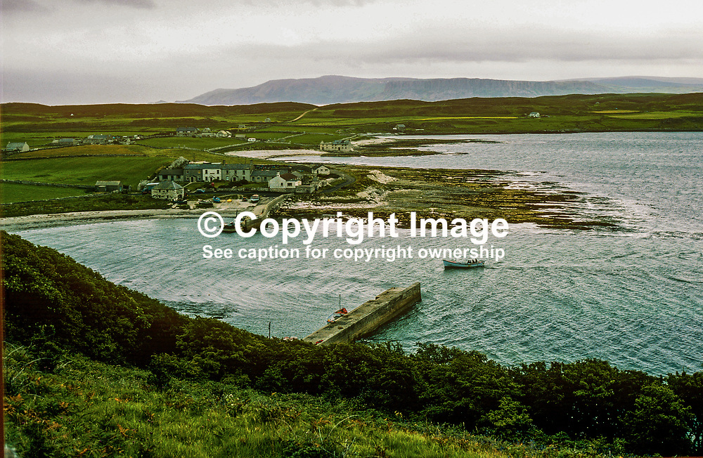 General view, Rathlin Island, N Ireland, harbour, Church Bay, with the Co Antrim coastline in the distance. 197809000241p..<br /> <br /> Copyright Image from Victor Patterson, Belfast, UK<br /> <br /> t: +44 28 9066 1296 (from Rep of Ireland 048 9066 1296)<br /> m: +44 7802 353836<br /> e: victorpattersonbelfast@gmail.com<br /> <br /> www.images4media.com<br /> <br /> Please see my full Terms and Conditions of Use at https://www.images4media.com/p/terms-conditions - it is IMPORTANT that you familiarise yourself with them.<br /> <br /> Images used online incur an additional cost. This cost should be agreed in writing in advance. Online images must be visibly watermarked i.e. © Victor Patterson or that of the named photographer within the body of the image. The original metadata must not be deleted from images used online.<br /> <br /> This image is only available for the use of the download recipient i.e. television station, newspaper, magazine, book publisher, etc, and must not be passed on to a third party. It is also downloaded on condition that each and every usage is notified within 7 days to victorpattersonbelfast@gmail.com.<br /> <br /> The right of Victor Patterson (or the named photographer) to be identified as the author is asserted in accordance with The Copyright Designs And Patents Act (1988). All moral rights are asserted.