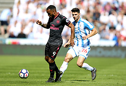 Arsenal's Alexandre Lacazette (left) and Huddersfield Town's Christopher Schindler battle for the ball