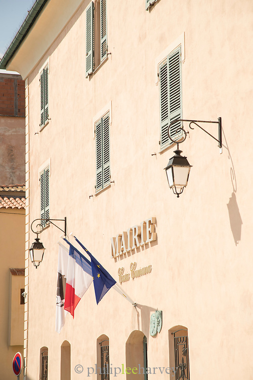 Close up of Town Hall building part with windows and flags, Llle-Rousse, Corsica, France