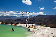 Tourists relax and swim at Hierve el agua - a natual geological formation in Oaxaca, Mexico. It is one of very few in the World where mineral deposits from the water have formed the shape of a waterfall made out of rock.