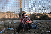 Lesbos, Greece, 9/12/20   A woman and her child are crying against the fences of the newly constructed refugee camp after the Moria camp was fully turned to ashes after a massive fire. Most of them fear that the new camp will be even worse than the old one and do not want to move there.