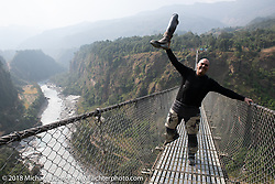 Dave Nolan (a licensed bridge inspector) on the Kusma Gyadi Bridge, the tallest (443') and one of the longest (1,128') suspension bridges in the country, on Day-7 of our Himalayan Heroes adventure riding from Tatopani to Pokhara, Nepal. Monday, November 12, 2018. Photography ©2018 Michael Lichter.
