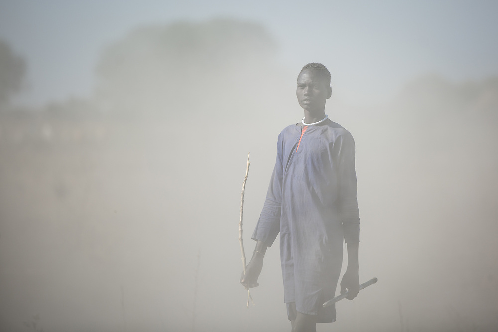 A young cattle keeper, wearing traditional clothes, walks alongside his herd. In some areas of South Sudan, cows are everything, and before all a source of money. If someone gets sick, a cow can be sold to buy treatment. South Sudan, 2020.