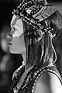Profile portrait of confidently posed young ethnic girl in Buon Me Thuot area, Vietnam, Southeast Asia. She wears beaded jewelry and leaves in her hair.