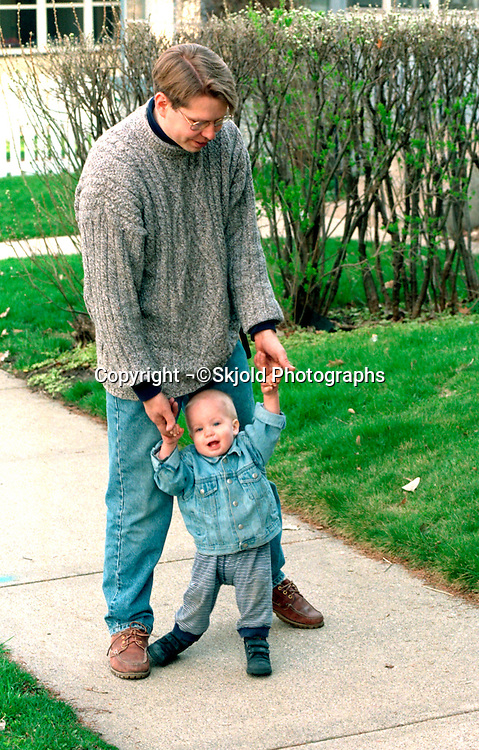 Father walking holding son's hands ages 35 and 2.  St Paul Minnesota USA