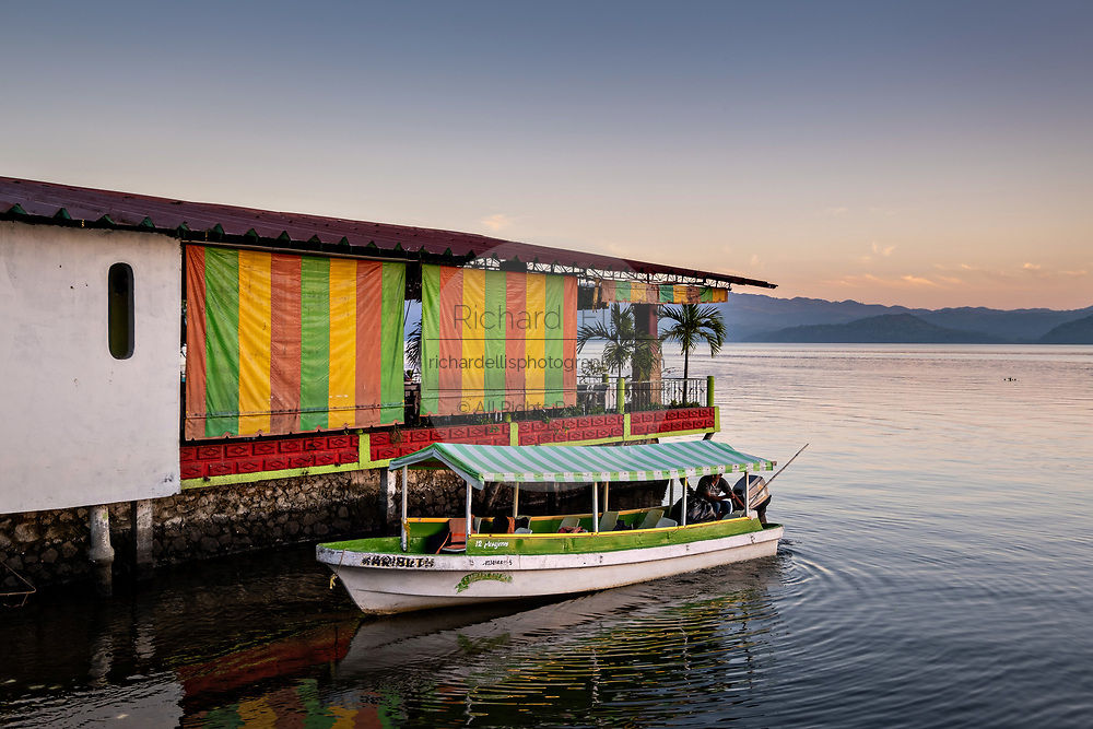 A water taxi called a Panga tied up at a waterfront restaurant in Lake Catemaco at sunset in Catemaco, Veracruz, Mexico.  The tropical freshwater lake at the center of the Sierra de Los Tuxtlas, is a popular tourist destination and known for free ranging monkeys, the rainforest backdrop and Mexican witches known as Brujos.