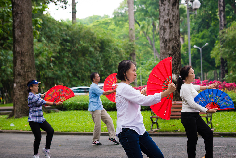Group practicing thai chi with fans in Tao Dan Park, Saigon