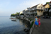 Two children (9 years old and 5 years old) walking along road with cat, Racisce, island of Korcula, Croatia