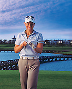 Female professional golfer Annika Sorenstam points her golf club at the camera and smiles