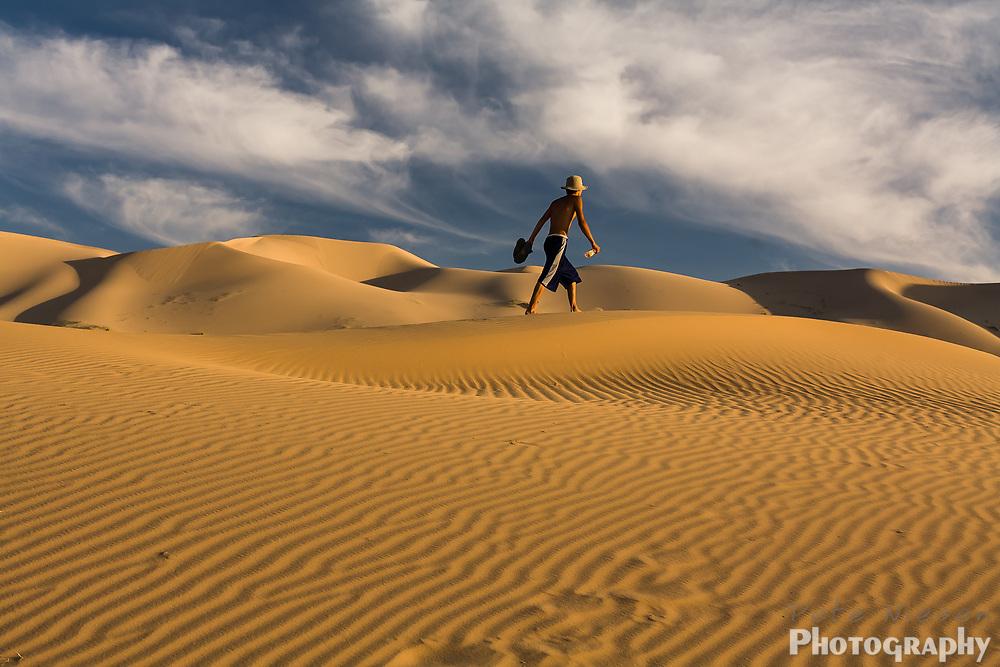 Mongolian man walking alone across dunes of Gobi Desert
