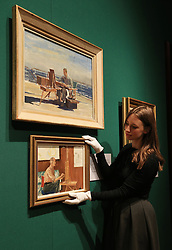 An employee of the Royal Collection Trust adjusts the Duke of Edinburgh's Seago Painting which sits below Edward Seago's HRH The Duke of Edinburgh painting on the desk of HMY Britannia, which are on display in the Portrait of the Artist exhibition at the Queen's Gallery, Buckingham Palace, London.