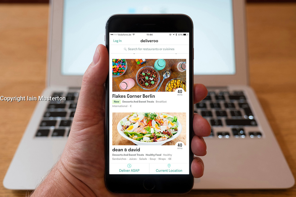 Using iPhone smartphone to display restaurants featured  in  Deliveroo food home delivery service in Berlin, Germany