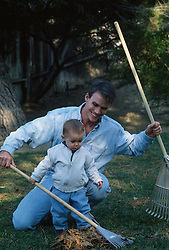 Man teaching little boy how to rake leaves