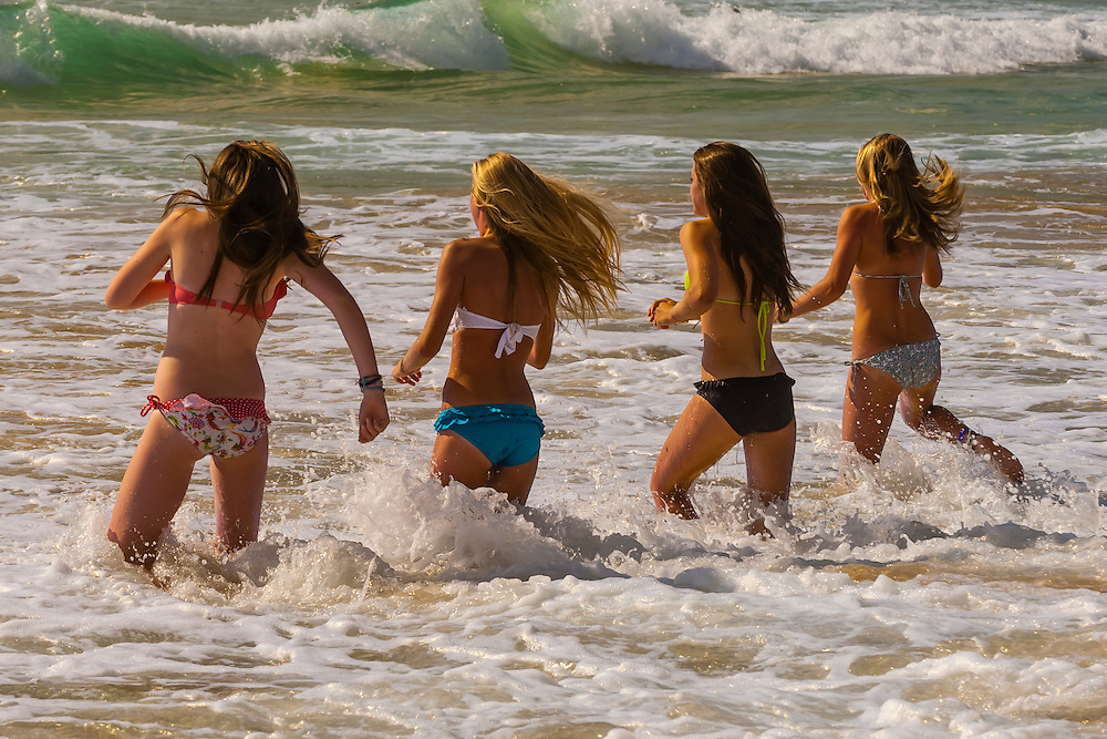 Teenaged girls running in the surf at Manly Beach, Sydney, New South Wales, Australia.