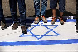 June 23, 2017 - Gaza City, Gaza Strip - Palestinian children stand on a make shift Israeli flag in a protest against annual al-Quds Day or Jerusalem Day, following Friday prayer in Gaza. (Credit Image: © Ashraf Amra/APA Images via ZUMA Wire)