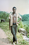 Full length portrait of young man standing with shirt open showing his chest, rural location, Jamaica, 1970
