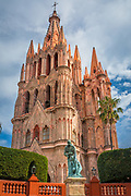 La Parroquia de San Miguel Arcángel church in the historic center of San Miguel de Allende, Mexico<br /> ------<br /> La Parroquia de San Miguel Arcángel, the current parish church of San Miguel, is unique in Mexico and the emblem of the town. It has a Neo-gothic façade with two tall towers that can be seen from most parts of town. It is one of the most photographed churches in Mexico. The church was built in the 17th century with a traditional Mexican façade. The current Gothic façade was constructed in 1880 by Zeferino Gutierrez, who was an indigenous bricklayer and self-taught architect. It is said Gutierrez's inspiration came from postcards and lithographs of Gothic churches in Europe; however, the interpretation is his own and if more a work of imagination than a faithful reconstruction. In front of this façade is a small atrium, which is guarded by a wrought iron fence. There is a monument in the atrium dedicated to Bishop José María de Jesús Diez de Sollano y Davalos. The San Rafael or Santa Escuela Church is located to the side of the parish. It was founded by Luis Felipe Neri de Alfaro in 1742. The main façade has two levels with arches, pilasters, floral motifs and a frieze on the first level. The second level has a choir window framed by pink sandstone. The bell tower is Moorish. According to legend, this older chapel was the site of the first Christian ceremony in San Miguel.