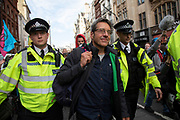 George Monbiot is arrested and taken away by police after a directive from the police not to gather, Extinction Rebellion took over Whitehall in a sit down protest where large numbers were arrested on 16th October 2019 in London, England, United Kingdom. George Joshua Richard Monbiot is a British writer known for his environmental and political activism. Extinction Rebellion is a climate change group started in 2018 and has gained a huge following of people committed to peaceful protests. These protests are highlighting that the government is not doing enough to avoid catastrophic climate change and to demand the government take radical action to save the planet.