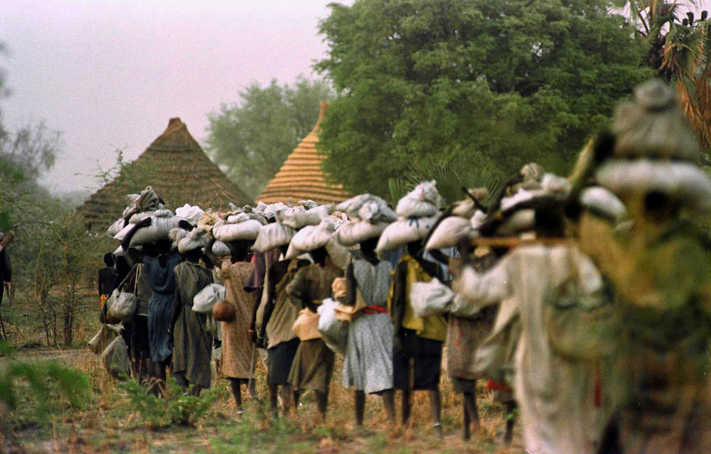 csz980429sudan1c:Women are given the job of dividing their World Vision food ration among their family members,  famine conditions in Bahr El Ghazal region of southern Sudan threaten the lives of 500,000 people: pic Craig Sillitoe.S..Picture taken on trip to the Sudan sponsored by World Vision melbourne photographers, commercial photographers, industrial photographers, corporate photographer, architectural photographers, This photograph can be used for non commercial uses with attribution. Credit: Craig Sillitoe Photography / http://www.csillitoe.com<br /> <br /> It is protected under the Creative Commons Attribution-NonCommercial-ShareAlike 4.0 International License. To view a copy of this license, visit http://creativecommons.org/licenses/by-nc-sa/4.0/.