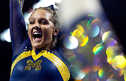 Lexi Funk of the Michigan Wolverines celebrates after completing her beam routine at the Elevate the Stage meet at the Huntington Center on February 23, 2019 in Toledo, Ohio.