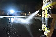 Nederland, Millingen, 20-2-2018Het Oranjeplein wordt door de brandweer onder water gezet. De komende nachten herhalen ze dit zodat er een mooie ijsvloer kan groeien waarop bewoners kunnen schaatsen.Foto: Flip Franssen