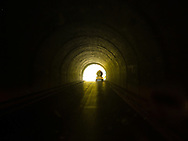 a tanker trailer truck exits a tunnel as seen from inside the tunnel.