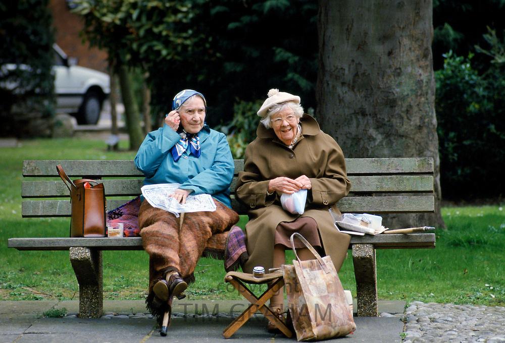 Elderly retired women sitting on a park bench and enjoying a picnic, England, UK