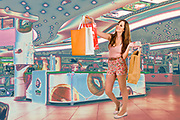 Digitally manipulated image of a young woman in her twenties out shopping in the mall with shopping bags