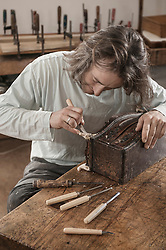 Carpenter restoring an antique bone box at workshop, Bavaria, Germany